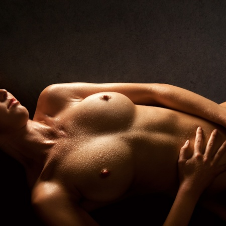 Breasts of a beautiful nude woman lying in front of dark background