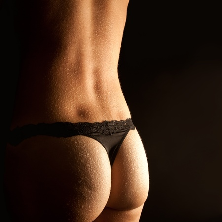 woman nude standing: Beautiful wet female bottom in black panties in  front of black background