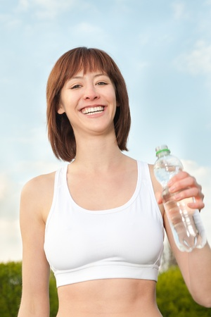 Beautiful athletic woman with bottle of mineral water under blue sky photo