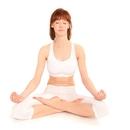 Young woman practicing yoga in the lotus position, in front of white background photo
