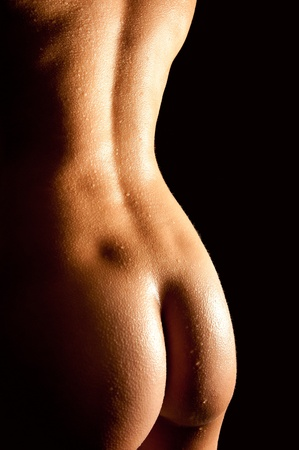 Female curves of a beautiful nude woman in front of black background Stock Photo - 9746113