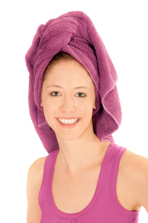 Closeup portrait of beautiful young woman with towel on her head after washing her hair, isolated on white photo
