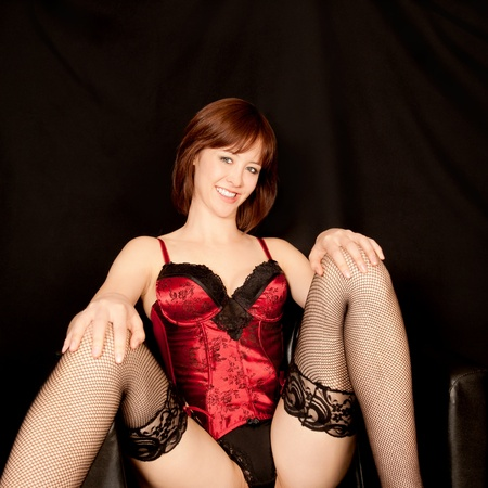 Portrait of a beautiful woman in erotic underwear sitting in black armchair Stock Photo - 9832893