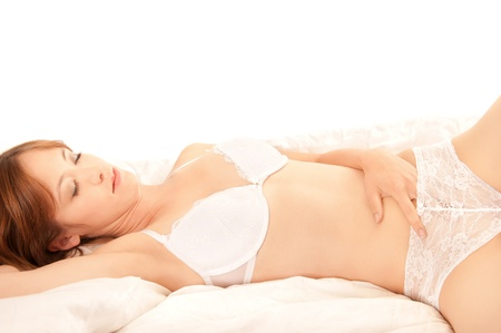 Portrait of a beautiful woman in underwear lying on white bed caressing herself with closed eyes