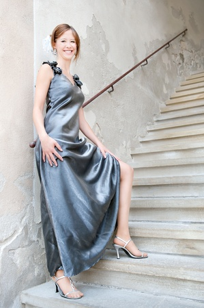 Full length fashion portrait of a beautiful young woman in silver dress and high heels in front of ancient stairs Stock Photo