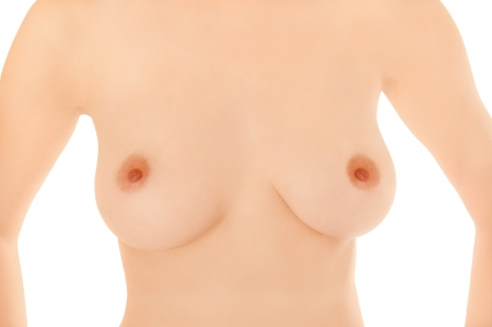Beautiful breasts of a young woman in front of white background