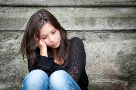 beautiful crying woman: Outdoor portrait of a sad teenage girl looking thoughtful about troubles