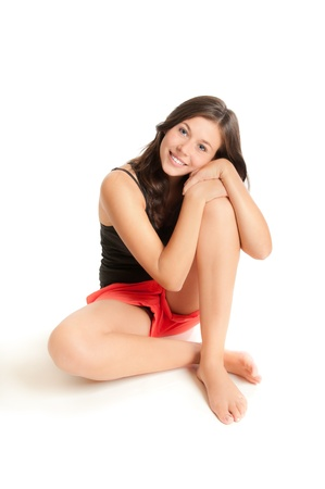 nude girl sitting: Beautiful young woman in red shorts and black top in front of white background  Stock Photo