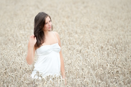 Outdoor portrait of a beautiful young woman in a grainfield in summer photo