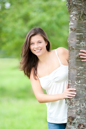 Outdoor portrait of a cute teen behind a tree in summer