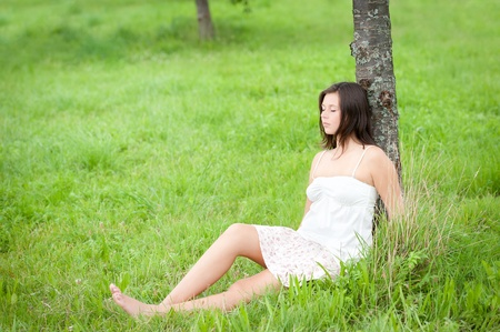 Outdoor portrait of a cute teen resting with closed eyes under a tree photo