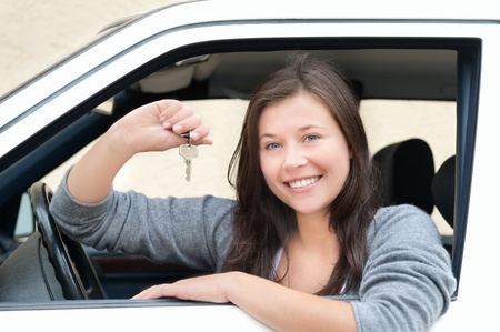 Young woman sitting in car and showing key. She is happy about her new drivers license or new car