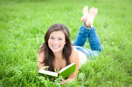 Outdoor portrait of a cute teen reading a book while lying in green grass photo
