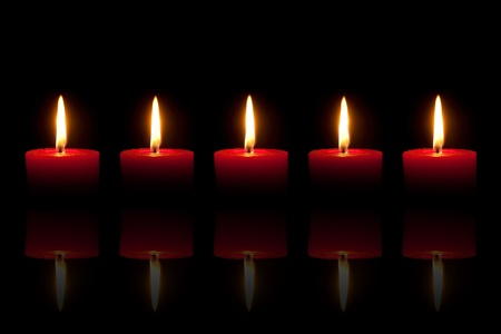 Five burning red candles in front of black background, with reflection photo