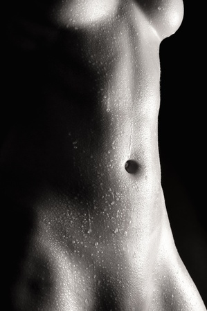 Wet abdomen of a nude young woman in front of black background, monochrome Stock Photo - 10278461