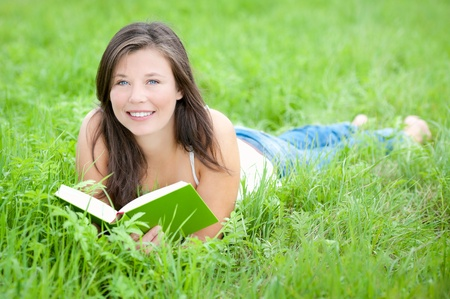 Outdoor portrait of a cute teen reading a book while lying in green grass 版權商用圖片