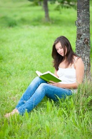 Outdoor portrait of a cute teen sitting under a tree and reading a book