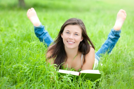 Outdoor portrait of a cute teen reading a book while lying in green grass  Stock Photo