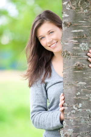 Outdoor portrait of a cute teen behind a tree in summer Stock Photo - 10683909