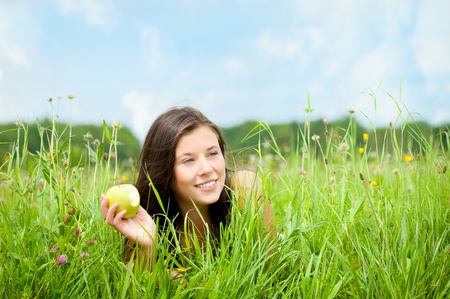 Portrait of a beautiful woman lying in a meadow in summer and eating an apple