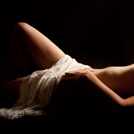 Classical nude of a beautiful young woman lying in front of black background covered with a white towel