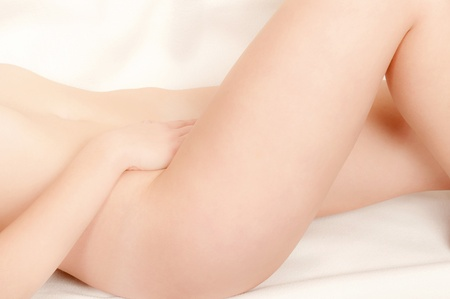 anatomy nude: Classical closeup of a beautiful nude woman lying on white bed  Stock Photo