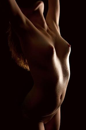 wet nude: Hermosa joven mujer desnuda con el cuerpo mojado en frente de fondo negro