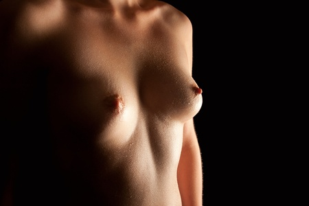 Beautiful wet breasts of a young woman in front of black background Stock Photo - 10833575