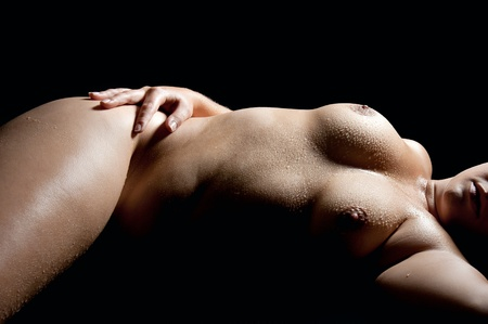 Nude wet torso of a beautiful young woman in front of black background  Stock Photo
