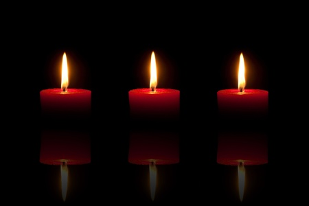 Three burning red candles in front of black background, with reflection Stock Photo - 10965990
