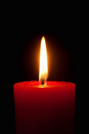 Closeup of a burning red candle in front of black background 版權商用圖片