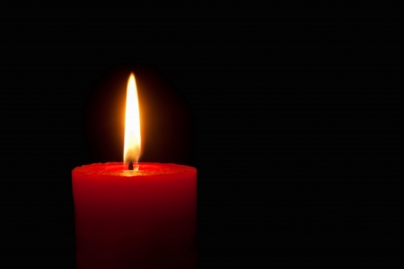 1 object: Closeup of a burning red candle in front of black background Stock Photo
