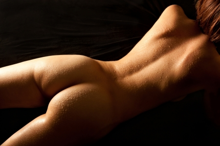 Nude young woman with wet body lying on black mattress, closeup of her beautiful back