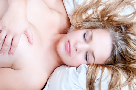 nude blond: Beautiful nude blond woman sleeping on white bed hiding her breast with her hand