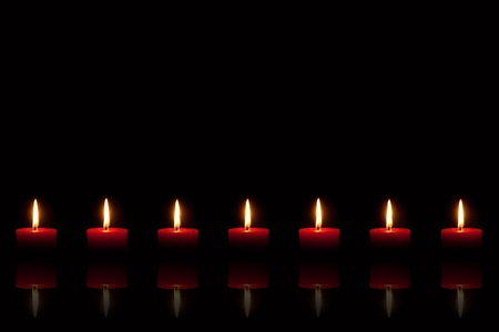 Row of seven burning red candles in front of black background, with reflection Standard-Bild