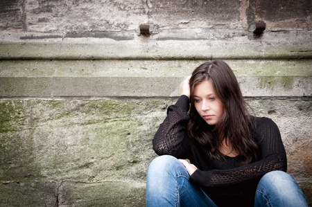 Outdoor portrait of a sad teenage girl looking thoughtful about troubles  photo