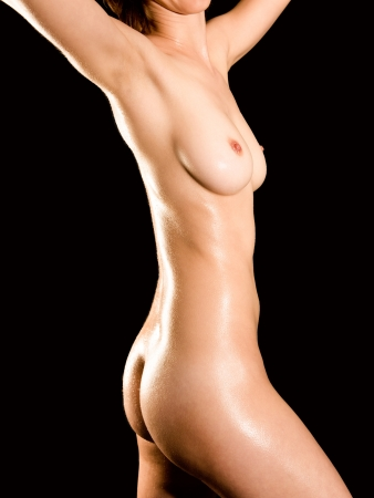 Closeup of a nude wet female body in front of black background photo