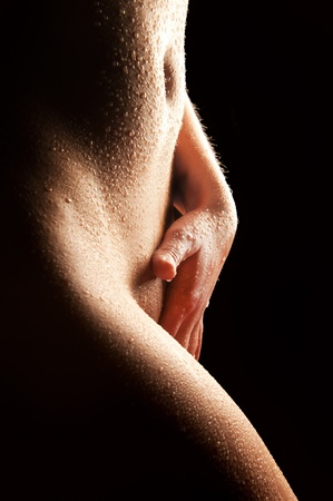 Nude wet body of a sexy woman touching herself in front of black background Stock Photo - 11077050