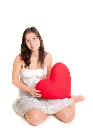 Portrait of cute teenage girl holding red heart pillow, in front of white background photo