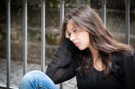 verdrietig meisje: Outdoor portret van een droevig tienermeisje op zoek doordachte over problemen