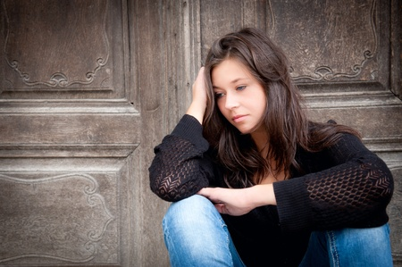Outdoor portrait of a sad teenage girl looking thoughtful about troubles Stock Photo