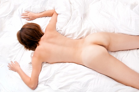 Beautiful back of nude young woman lying on white bed  Stock Photo
