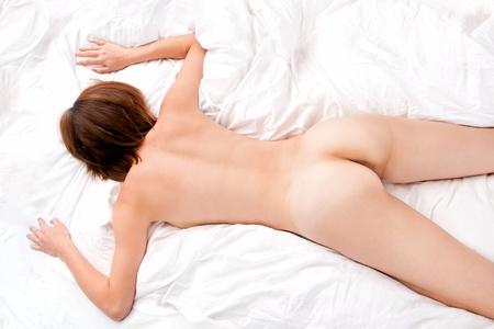 nudo di donna: Torna bella di nudo giovane donna sdraiata sul letto bianco Archivio Fotografico