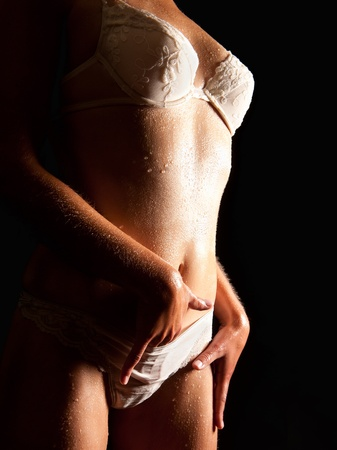 Wet body of a sexy young woman in beautiful white underwear caressing herself in front of black background
