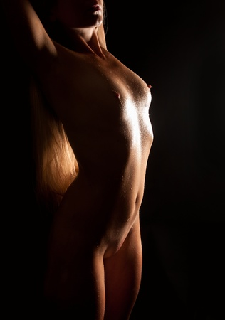 Beautiful nude blond woman with wet body in front of black background