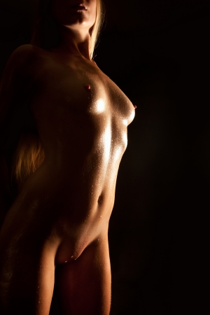 nude blond: Beautiful nude blond woman with wet body in front of black background