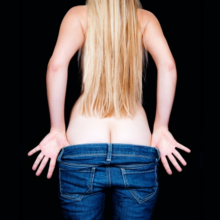 Bottom of a beautiful young woman with long blond hair undressing her blue jeans in front of black background Stock Photo - 11234492