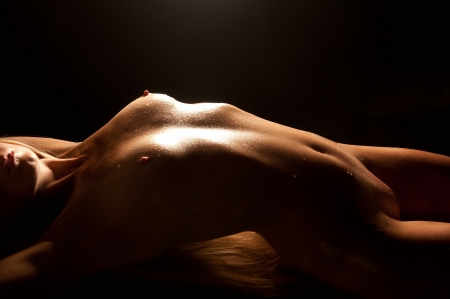 Beautiful nude blond woman with wet body lying in front of black background