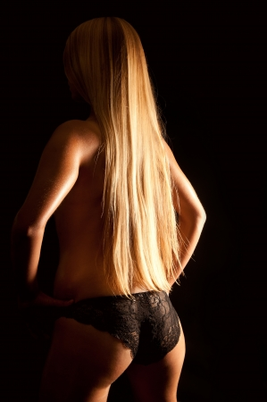 Beautiful back of a nude woman with long blond hair wearing black undies in front of black background  photo