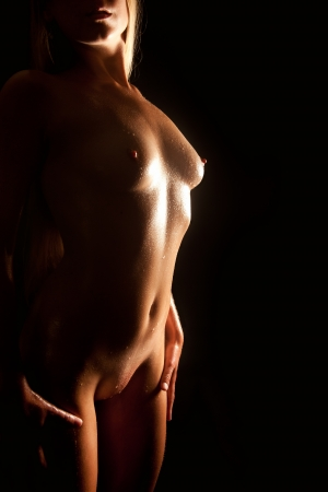 Beautiful nude blond woman with wet body in front of black background Stock Photo - 11234501
